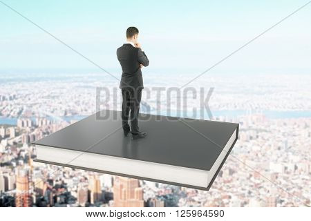 Businessman standing on a black book soaring over city