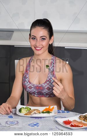 young fit woman in the kitchen with two plates of healthy food: rice chicken grill broccoli carrots mushrooms salmon tomato red peppers