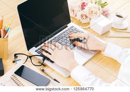 Female hands using laptop with blank screen on wooden desktop with flowers and office tools. Mock up ** Note: Shallow depth of field