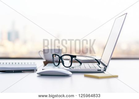 Sideview of office desk with laptop glasses and other items