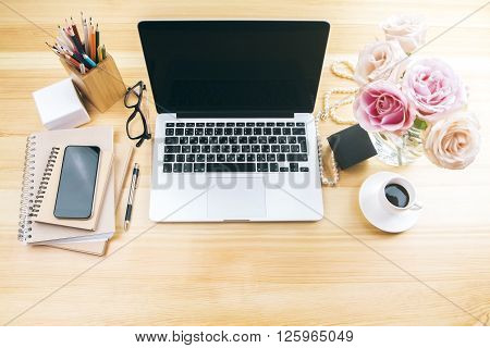 Girly office desktop with blank laptop screen flowers coffee smartphone and various office tools. Mock up