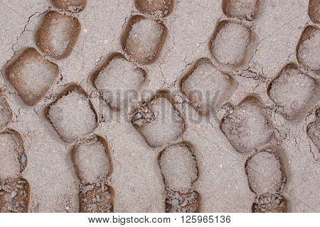 Sand background. The trail tread.Truck. Dirt road.The texture of the sand with the imprints of human activity.