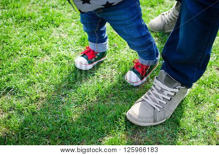 Walking toddler concept - little baby child boy making first step holding father's hand. First steps. Foot of father and son in stylish sneakers on the background of green grass. Copy space.