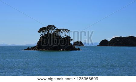 Back lit island with trees in the Abel Tasman National Park. Silhouette of a small island in New Zealand. Nature background.