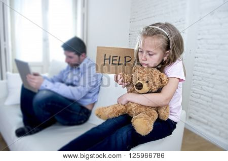 young internet addict father using digital tablet pad ignoring little sad daughter looking bored hugging teddy bear abandoned and disappointed with her dad asking for help