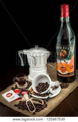 Trieste, Italy - April 16, 2016: Cup of coffee beans, moka, spoon and cinnamon on jute canvas. Pascucci coffee is worldwide coffee roasting company, its espresso is very popular in the world.