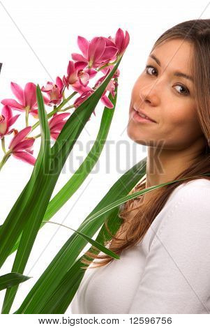 Brunette Woman Smelling Purple Orchid Flower