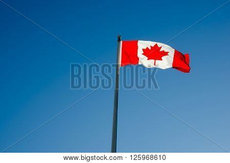 Canadian flag waving over blue sky in Ottawa