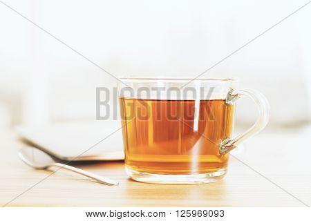 Wooden desktop with cup of tea and teaspoon