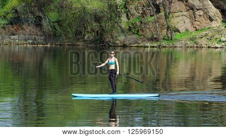 slim athletic woman in wetsuit stand up paddle board near the shore