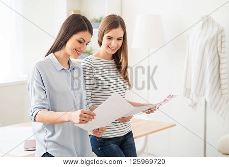 Like what you do. Cheerful positive beautiful smiling girl holding cards with colors and expressing gladness while leaning on the table