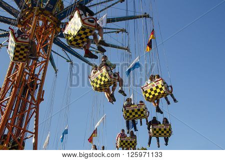 MUNICH, GERMANY - OCTOBER 02, 2015: Carousel in motion with people flying through the air on Theresienwiese