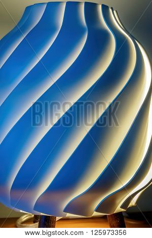 Spiral pattern desk lamp that has been turned on. The environmental lighting gave the lamp a white, yellow and blue coloration.