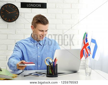 Young man showing passports with tickets in the office of travel company