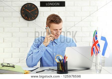 Young man talking on the smart phone in the office of travel company