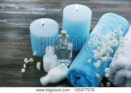 Spa still life with rolled towels and candlelight on wooden background