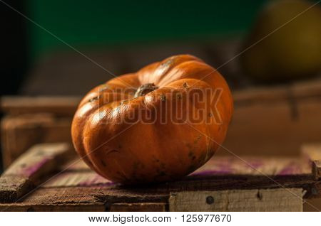 A yellow big pumpkin placed on a wooden crate in farmers market.