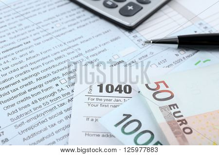 1040 Income Tax Form and euro bills, close up