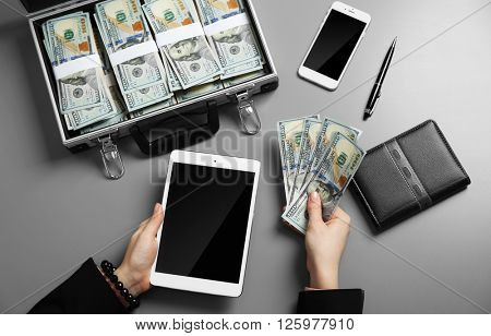 Businesswoman with tablet and case full of money