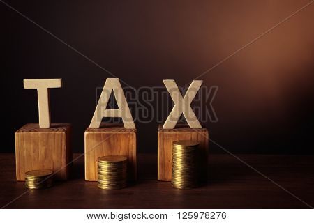 Word tax with stacked coins on dark background