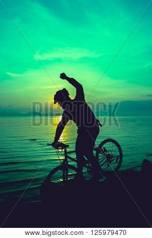 Silhouette of bicyclist riding the bike on rocky trail at seaside on colorful sunset sky background. Active outdoors lifestyle for healthy concept. Action of winner or successful people. Emerald green tone.