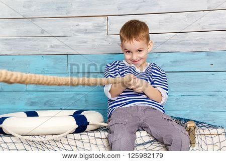 little boy pulling a rope looking at camera