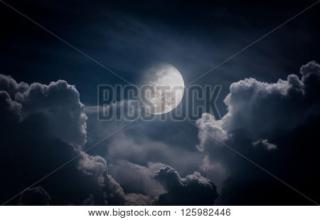 Attractive photo of a nighttime sky with clouds bright full moon would make a great background. Nightly sky with large moon. Beautiful nature use as background. Outdoors.