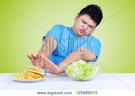 Portrait of an overweight person refuse to eat a plate of junk food on the table