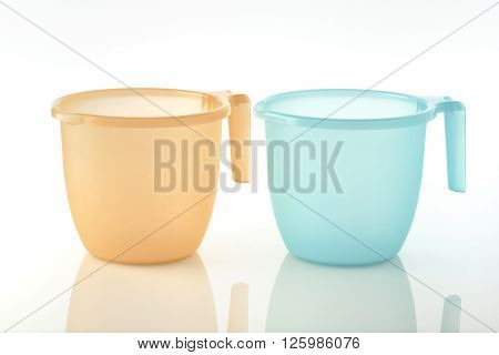 Bathroom Mugs / High resolution image of orange and turquoise plastic bathroom mugs.