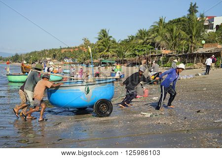 MUI NE, VIETNAM - DECEMBER 25, 2015: Fishermen after the sea dragged round plastic boat ashore. The fishing harbor of Mui Ne, Vietnam