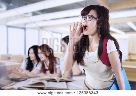 Female high school student screaming in the classroom while her friends studying together