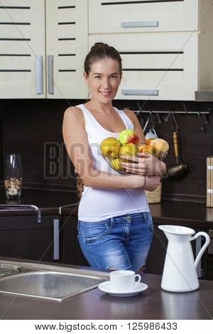 Young brunette woman with green apples on a plate on kitchen
