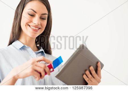 Color your life. Cheerful content positive beautiful girl holding tablet and smiling while expressing gladness