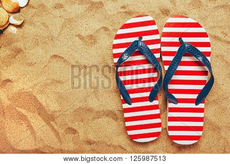 Pair of flip flops on beach sand top view of summer holiday vacation.