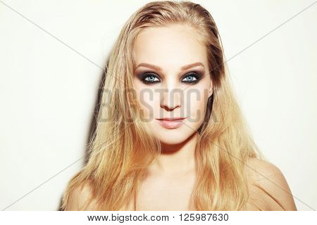 Vintage style horizontal portrait of young beautiful blond woman with long hair and smoky eyes