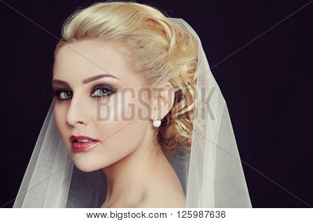 Vintage style portrait of young beautiful bride with smoky eyes make-up and bridal veil