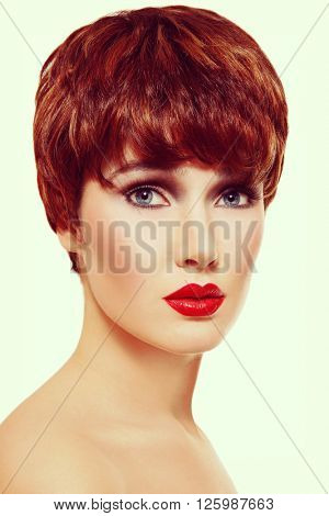 Vintage style portrait of young beautiful redhead woman with short haircut