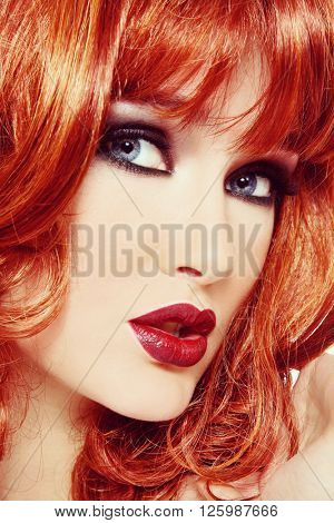 Vintage style close-up portrait of beautiful girl with smoky eyes makeup and long red hair