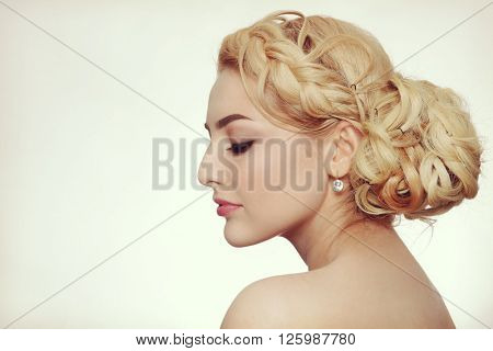 Vintage style profile portrait of young beautiful blond woman with fancy prom hairdo
