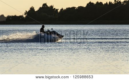 RAUMA, FINLAND ON JULY 03. View from the shore of a young unidentified guy cruising the inlet on July 03, 2013 in Rauma, Finland. Full speed ahead in the summer night. Editorial use.