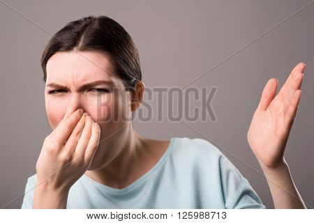 What a smell. Cheerless beautiful girl closing her nose and expressing disgust while standing isolated on grey background
