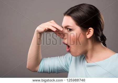 Terrible smell. Cheerless beautiful girl closing her nose and expressing disgust while standing isolated on grey background