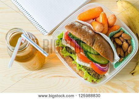 Vegan sandwich in lunch box with carrots and nuts - healthy food to go concept, wood background, copy space