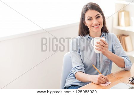 Get relaxation. Positive overjoyed nice smiling girl making notes and drinking tea while sitting at the table