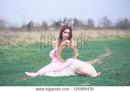 woman in a beautiful dress holding a mirror