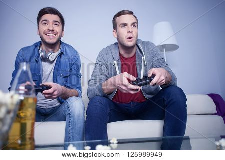 What a great game. Cheerful two friends are playing video games with joy. They are sitting on sofa. The man is smiling