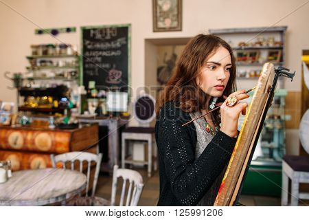 Hipster artist paints a painting in defocused cafe interior. Closeup of painting process in light art workshop interior. Creative  studious hipster woman painter paints in her studio picture.
