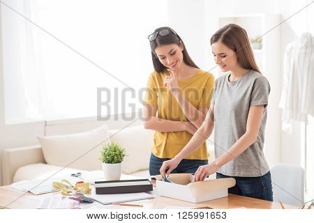 What is here. Cheerful delighted smiling girls standing near table and opening box while feeling glad