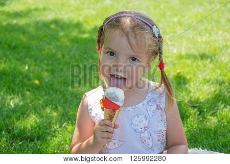 Pretty girl eating ice cream on a hot summer day