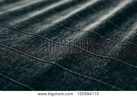 Abstract textured velvety dark background with diagonal lines. The texture.
